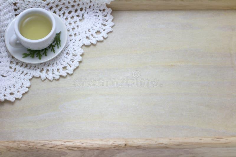 Bild der Tasse Tee und Doily mit hölzernem Hintergrund stockfoto
