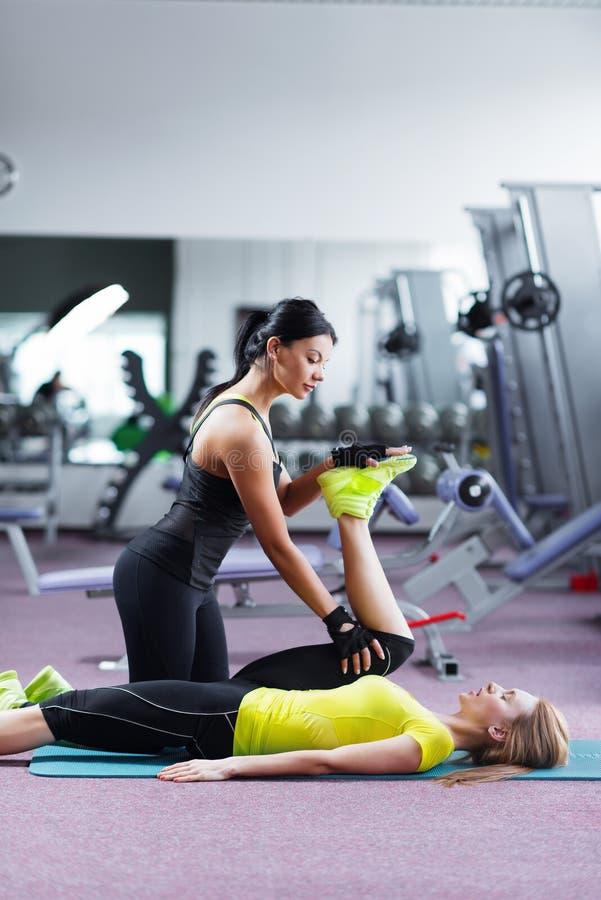 Bild der Trainerfrau ein Sitzmädchen ausdehnend lizenzfreie stockbilder