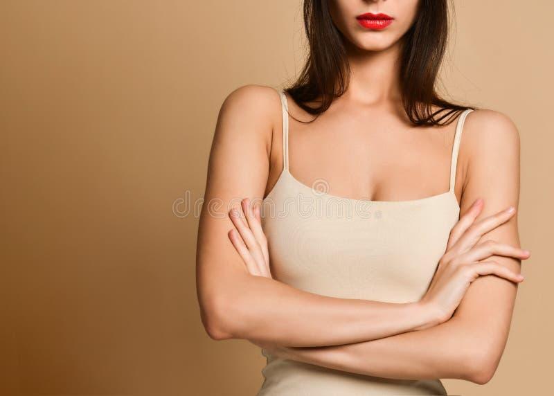 Bild der verärgerten Stellung der jungen Frau über nacktem Hintergrund Schauen der Kamera stockfotos