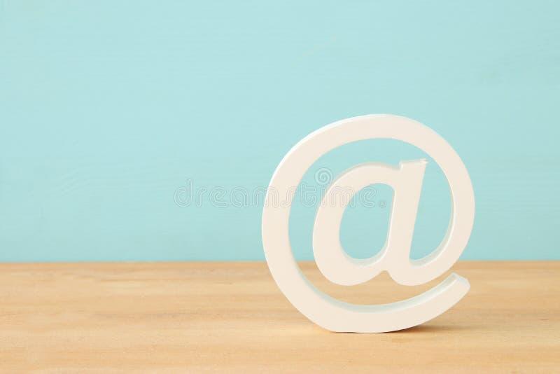 Bild der weißen Postikone über hölzernem Schreibtisch lizenzfreie stockfotografie