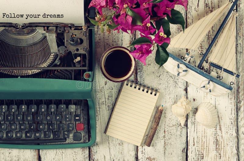 Bild der Weinleseschreibmaschine mit Phrase folgen Ihren Träumen, leeren Notizbuch, Tasse Kaffee und alten Segelboot lizenzfreie stockfotos