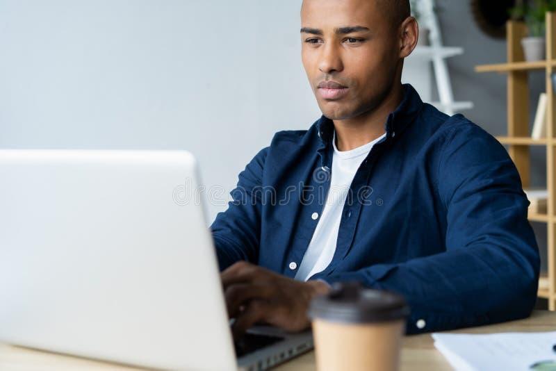 Bild des Afroamerikanergeschäftsmannes arbeitend an seinem Laptop Hübscher junger Mann an seinem Schreibtisch lizenzfreie stockfotografie