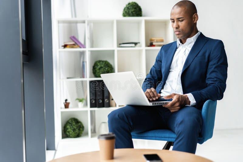 Bild des Afroamerikanergeschäftsmannes arbeitend an seinem Laptop Hübscher junger Mann an seinem Schreibtisch stockbilder