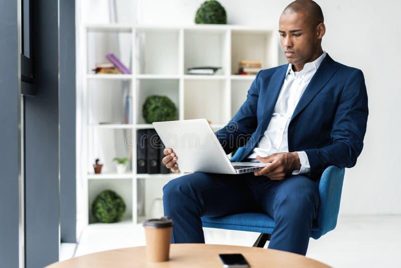 Bild des Afroamerikanergeschäftsmannes arbeitend an seinem Laptop Hübscher junger Mann an seinem Schreibtisch stockbild