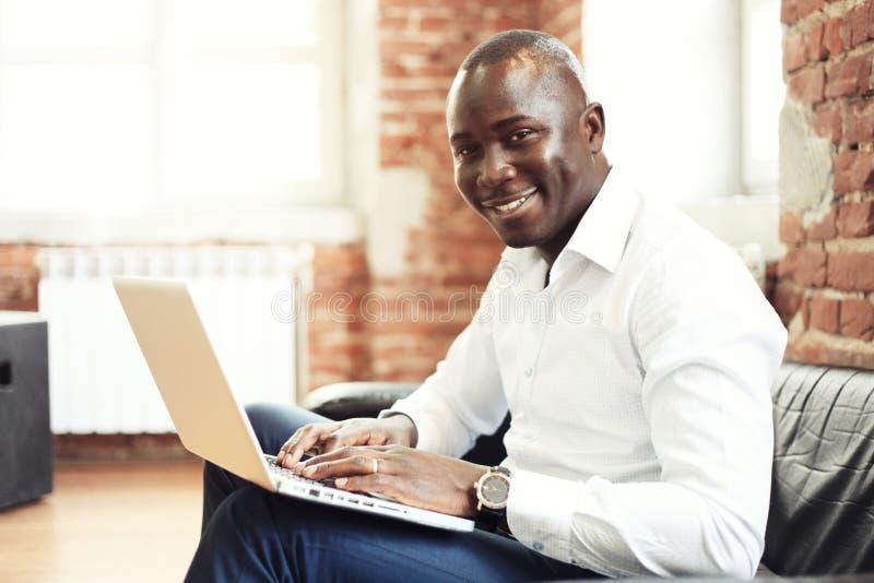 Bild des Afroamerikanergeschäftsmannes arbeitend an seinem Laptop Hübscher junger Mann an seinem Schreibtisch lizenzfreies stockfoto