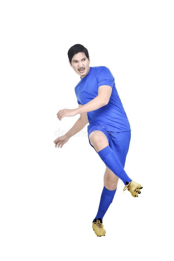 Bild des asiatischen Fußballspielermannes mit blauem Trikot in der Aktion lizenzfreies stockfoto