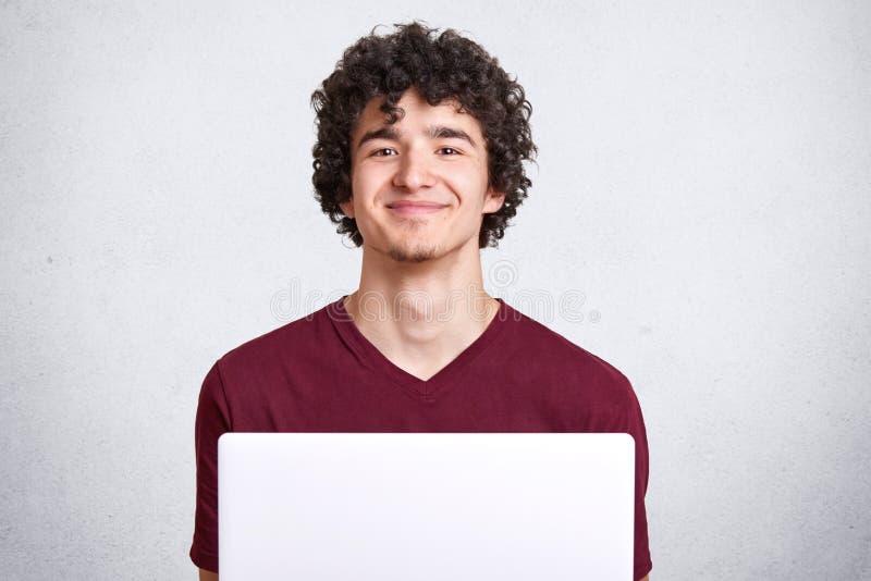 Bild des attraktiven jungen Kerls mit dem gelockten Haar, das zufälliges kastanienbraunes T-Shirt, sitzend vor dem offenen Laptop stockfotos