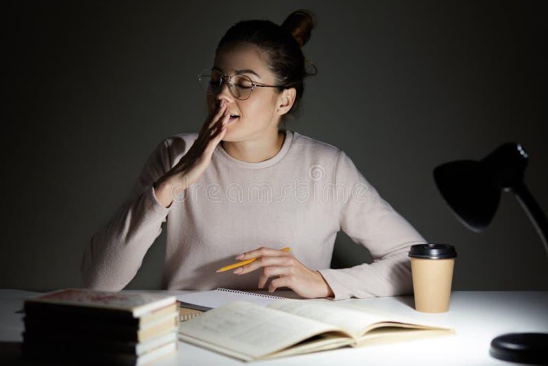 Bild des attraktiven seepy Studentengegähnes mit geschlossenen Augen, sitzt am Desktop beim Vorbereiten für Klassen, Arbeitsübers lizenzfreies stockbild