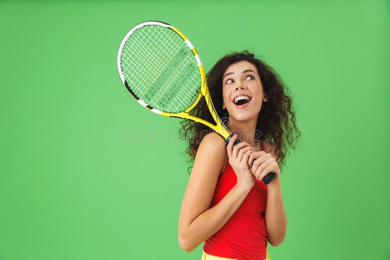 Bild des attraktiven weiblichen Tennisspielers 20s, der Schläger lächelt und hält stockfoto