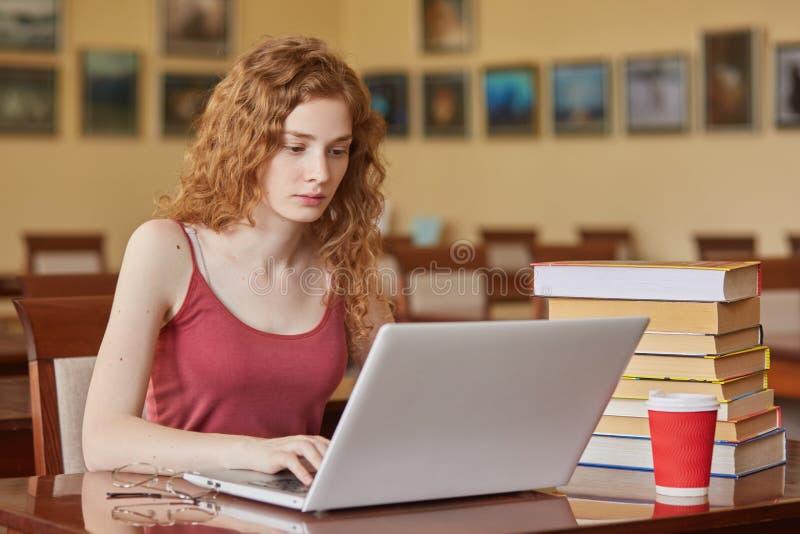 Bild des aufmerksamen durchdachten jungen Mädchens, das an ihrem Laptop in der Bibliothek, wegbrillen und die Schale des Getränks lizenzfreie stockfotos