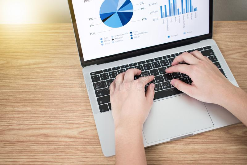 Bild des Datendiagramms in einer Laptop-Computer auf einem braunen h?lzernen Schreibtisch lizenzfreies stockfoto
