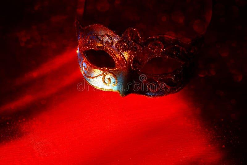 Bild des eleganten Blaus und des Goldes venetianisch, Karnevalmaske über rotem Hintergrund Magisches Funkeln ovrlay stockbild
