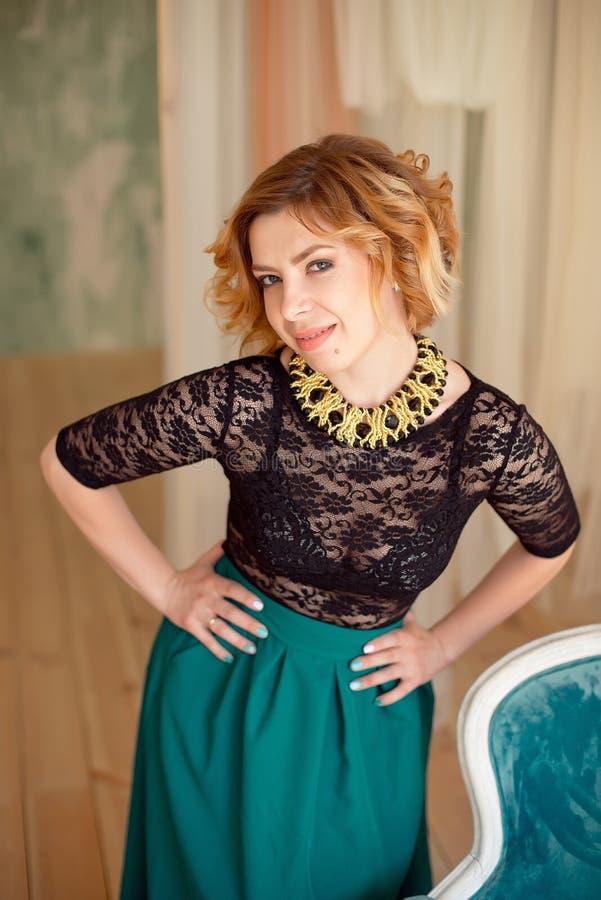 Bild des eleganten Mädchens sitzend im Retrostillehnsessel Redhaired gelocktes junges Modell stockbild