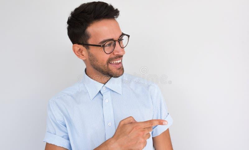 Bild des erfreuten unrasierten hübschen Mannes mit fröhlichem Ausdruck, Punkte beiseite, zeigt leeren Kopienraum für Ihre Werbung lizenzfreies stockbild