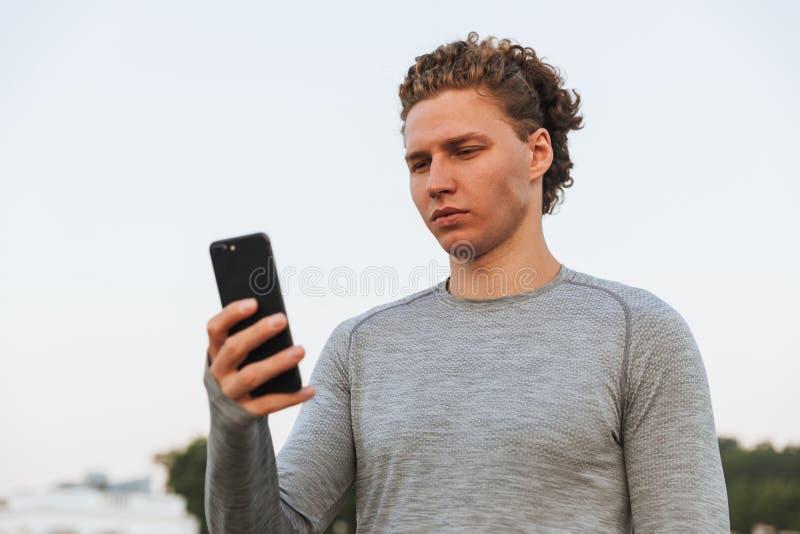 Bild des ernsten gelockten Sportlers, der Smartphone verwendet stockbilder