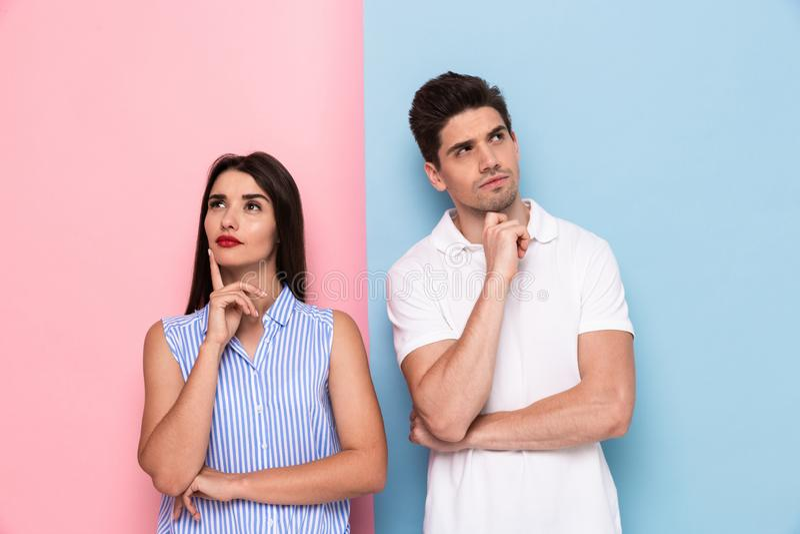 Bild des ernsten Mannes und der Frau in der Freizeitkleidung, die Kinne berührt und lizenzfreies stockbild
