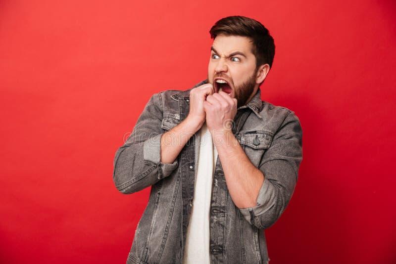 Bild des erschrockenen Mannes 30s in der Jeansjacke, die beiseite auf Spindel schaut stockbilder