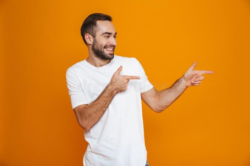 Bild des europäischen Kerls 30s im T-Shirt, das beiseite Finger bei der Stellung, über gelbem Hintergrund zeigt stockbilder