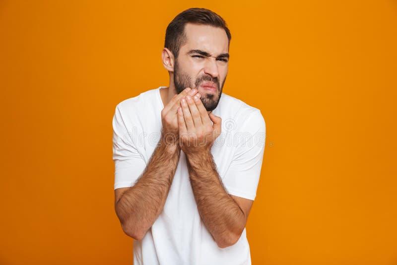 Bild des europäischen Mannes 30s im T-Shirt, das seine Backe berührt und unter Zahnschmerzen während, über gelbem Hintergrund lei lizenzfreie stockbilder