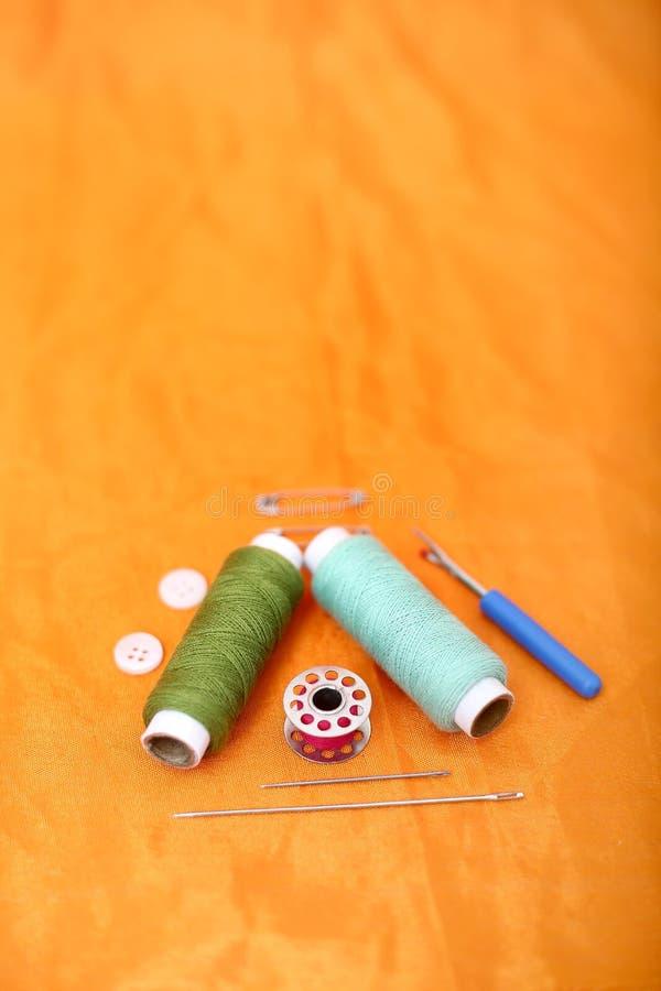 Bild des farbigen Nähgarns, der Nadel, der Spule, des Knopfes, der Sicherheitsnadel und der Nadeltrennmaschine lizenzfreie stockfotografie