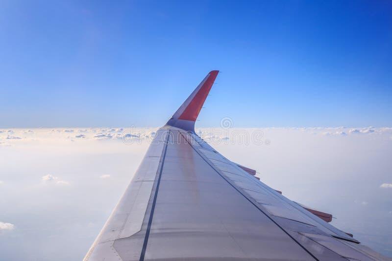 Bild des Flugzeugsitzes nahe bei Fenster mit weißer Wolke und blauem Himmel, Blick durch Flugzeugfenster lizenzfreie stockfotografie