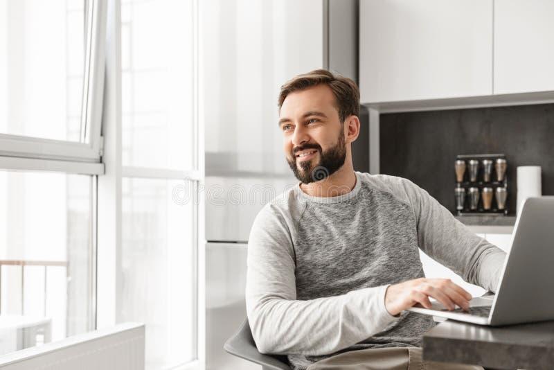 Bild des freudigen Mannes 30s im zufälligen Hemd, das an Laptop an h arbeitet stockfoto