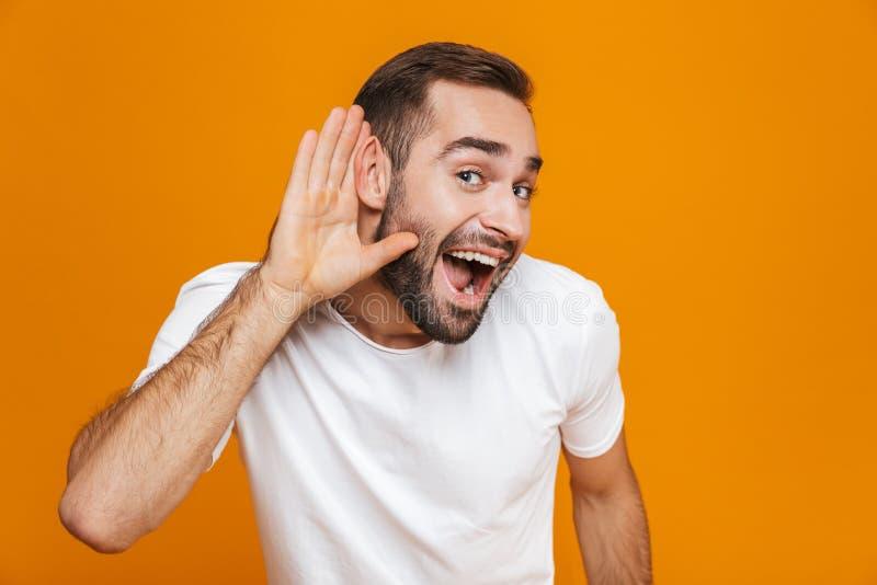 Bild des frohen Mannes 30s, der versucht, etwas beim Halten der Hand zu hören an seinem Ohr, über gelbem Hintergrund lizenzfreie stockfotografie