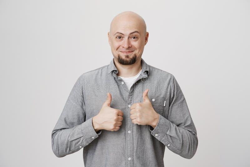 Bild des glücklichen hübschen Kerls im zufälligen grauen Hemd, das seine Daumen oben in anerkennend Geste über weißem Hintergrund stockbilder