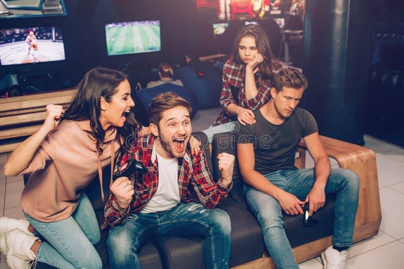 Bild des glücklichen Paars zujubelnd, während Sekunde umgekippt ist Sie Gewinn und verlorenes Spiel Kerle halten gamepads in den  stockfotos
