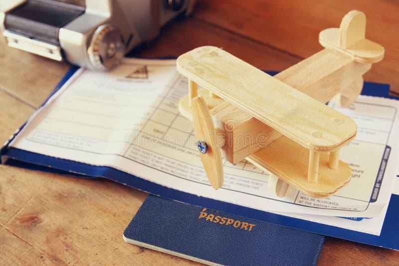 Bild des hölzernen Flugzeuges und des Passes der Fliegenkarte über Holztisch Retro- gefiltertes Bild lizenzfreie stockbilder