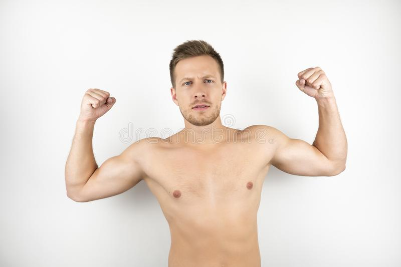 Bild des hübschen starken Mannes mit nackter Torsovertretung mischt weißen lokalisierten Hintergrund mit stockfotografie
