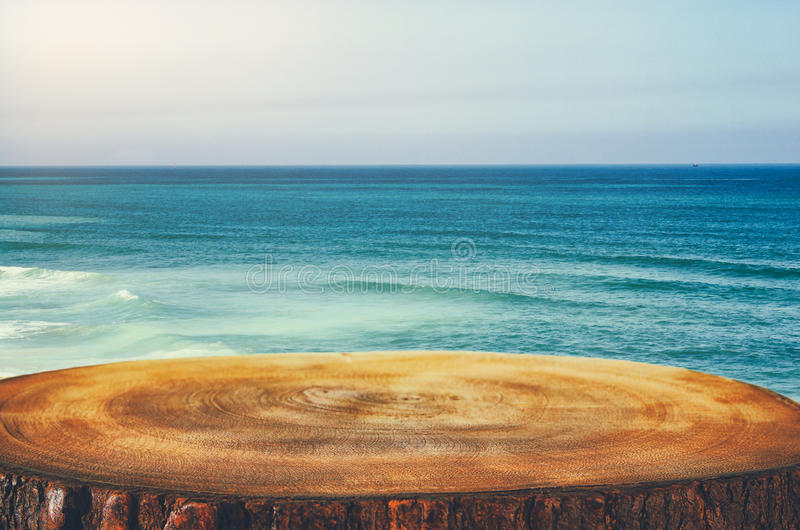 Bild des Holztischs im vorderen tropischen Seehintergrund für Produktanzeige und -darstellung stockbild
