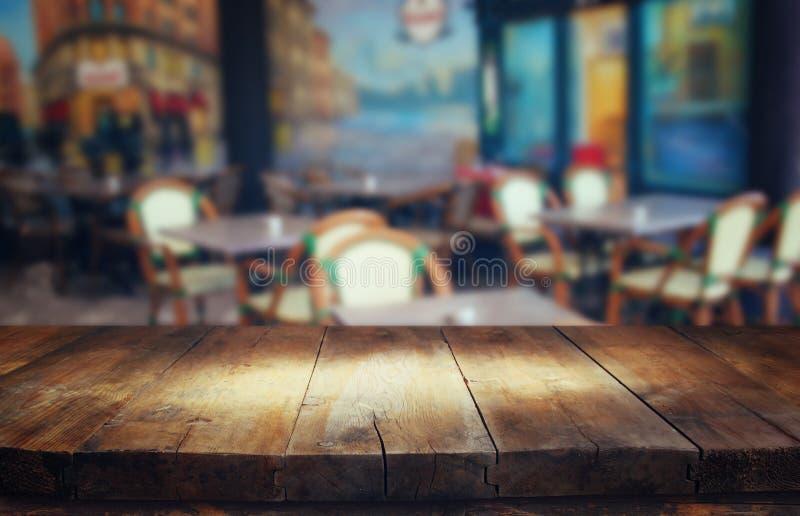 Bild des Holztischs vor Zusammenfassung verwischte Hintergrund von Restaurantlichtern stockfoto
