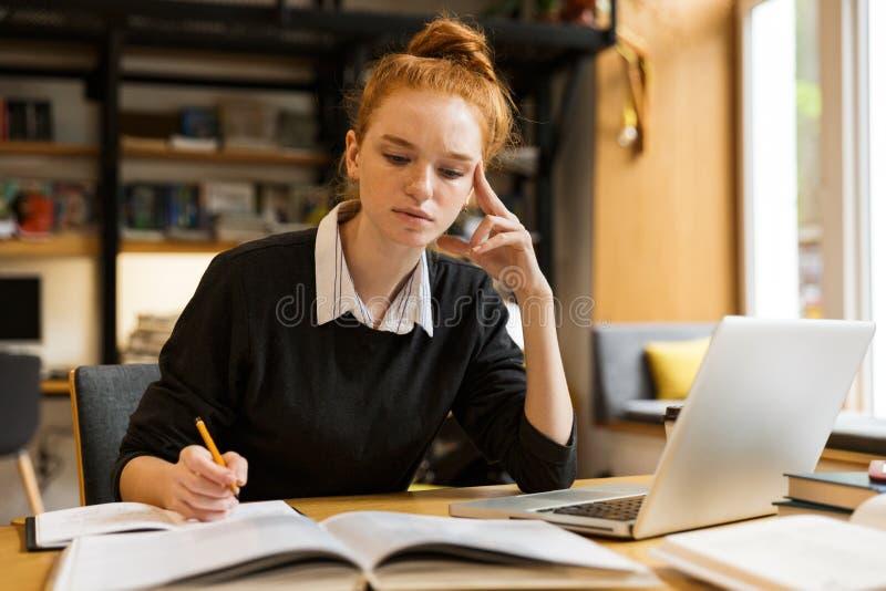 Bild des intelligenten Mädchens studierend, beim Sitzen am Schreibtisch in Col. lizenzfreie stockbilder
