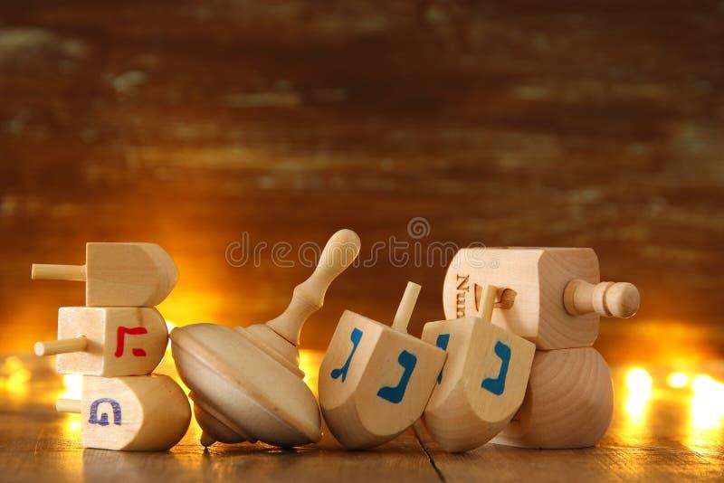 Bild des jüdischen Feiertags Chanukka mit hölzerner dreidels Sammlung u. x28; spinnendes top& x29; und glühende Goldlichter stockfotografie
