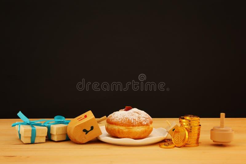 Bild des jüdischen Feiertags Chanukka mit traditionellem Donut und Kreisel auf dem Tisch