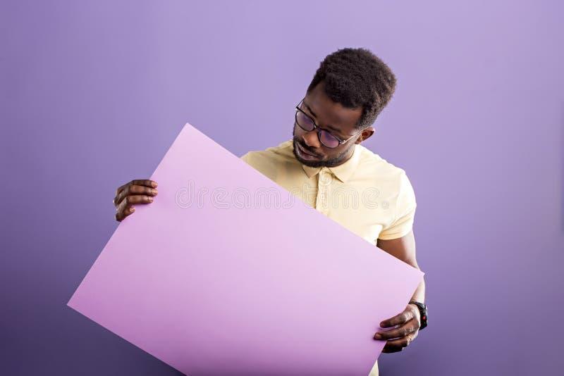Bild des jungen Afroamerikanermannes, der leeres Brett auf violettem Hintergrund h?lt stockfotografie