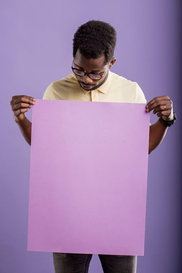 Bild des jungen Afroamerikanermannes, der leeres Brett auf violettem Hintergrund h?lt stockbild