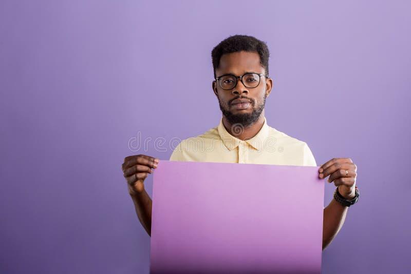 Bild des jungen Afroamerikanermannes, der leeres Brett auf violettem Hintergrund h?lt stockbilder