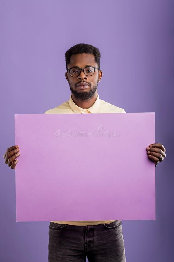 Bild des jungen Afroamerikanermannes, der leeres Brett auf violettem Hintergrund h?lt stockfoto