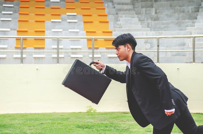 Bild des jungen Geschäftsmannes einen Aktenkoffer halten und auf den Wegen einer Bahn, Wettbewerbskonzept sprintend lizenzfreie stockfotos