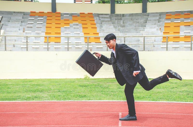 Bild des jungen Geschäftsmannes einen Aktenkoffer halten und auf den Wegen einer Bahn, Wettbewerbskonzept sprintend lizenzfreie stockfotografie