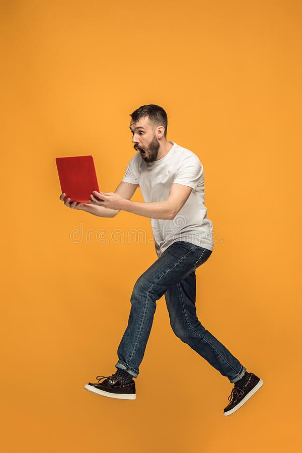 Bild des jungen Mannes über orange Hintergrund unter Verwendung der Laptop-Computers beim Springen stockfotos