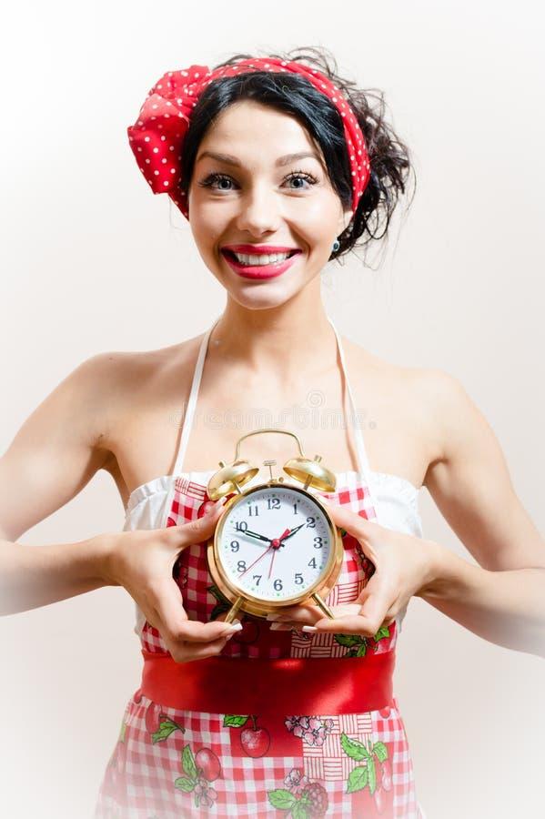 Bild des jungen schönen lustigen attraktiven Mädchens der jungen Frau des Pinup mit dem großen Lächeln, das den Wecker betrachtet lizenzfreie stockfotografie