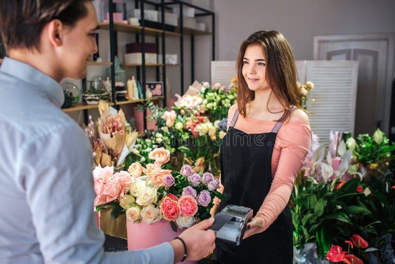 Bild des jungen weiblichen Floristen, der Geld therminal hält Sie steht vor Kunden Junger Geschäftsmannlohn für lizenzfreie stockfotografie