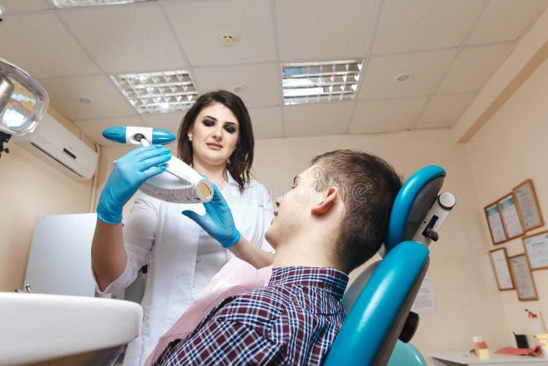 Bild des jungen weiblichen Zahnarztes im weißen Mantel, der mit männlichem Patienten im zahnmedizinischen Raum arbeitet stockbilder