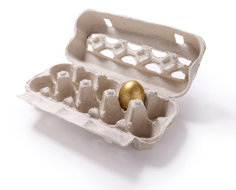 Bild des Kartonkastens mit einem goldenen Ei auf weißem backgr lizenzfreie stockbilder