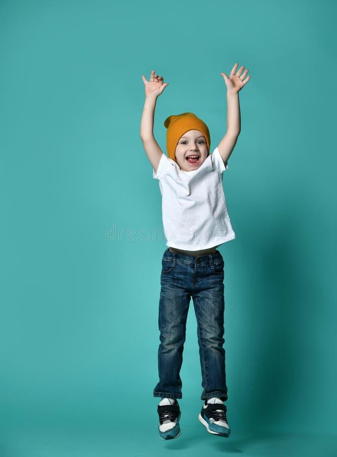 Bild des Kinderspringens des kleinen Jungen lokalisiert über grünem Hintergrund stockbild