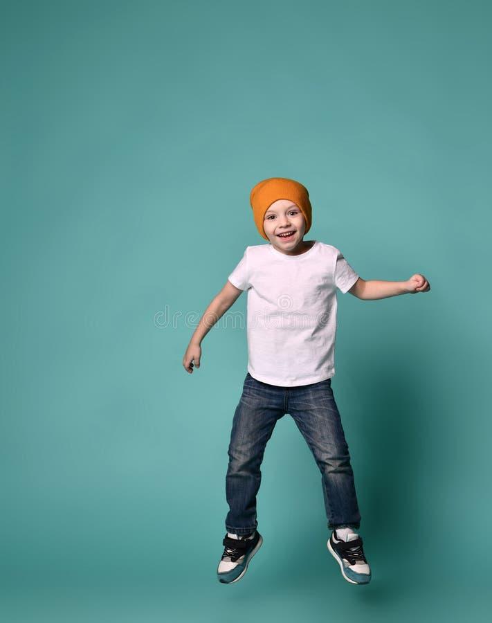 Bild des Kinderspringens des kleinen Jungen lokalisiert über grünem Hintergrund stockbilder