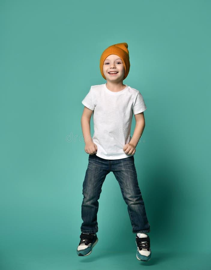 Bild des Kindes des kleinen Jungen, das über grünen Hintergrund springt lizenzfreies stockfoto